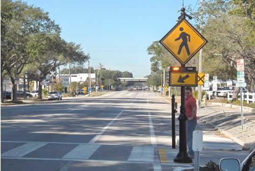 At-grade crossings are well-marked with the higher-visibility continental style of crosswalk and usually with accompanying W11-1 Bicycle Warning and W16-7p diagonal downward pointing arrow signs.