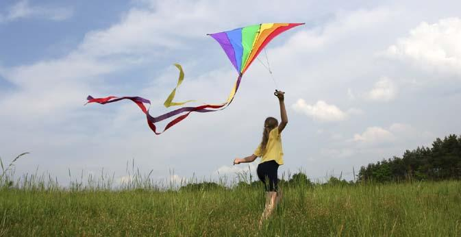 On a breezy day, take your kite to a flat, open area. Be sure that there are no power lines or big trees. Look at the ground around you. Is there anything you could trip over?