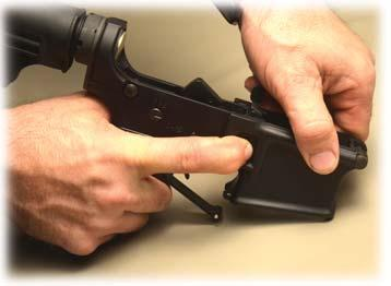 punch, or similar tool will work). 4) Allow the Trigger Guard to pivot down (Photo B) on its rear fixed pin.