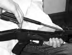 8. Remove the gas tube assembly and upper handguard from the rifle by holding the forward portion of the receiver with your left hand and rotating the gas tube lock arm upward until the flat face of