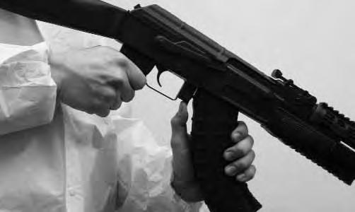 . To remove the magazine from the rifle while holding the rifle in the firing position, simply slide your left hand from the lower handguard to the magazine.
