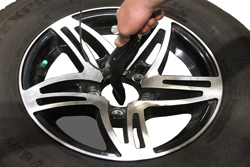 20A) or with a hand wrench, lower (counter-clockwise) or raise (clockwise) the tire.