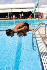One-part takeoff with forward dive tuck from poolside 1. Stand at the edge of the deck with your arms overhead. Focus on a target at a 45 angle across the pool.