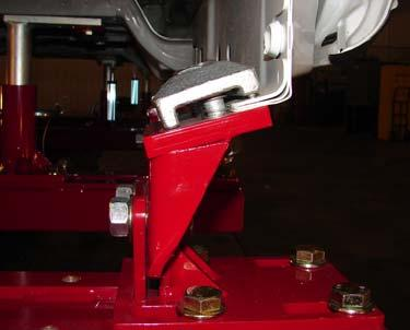 Lower the cab using the two-post lift until the anchor tubes can be pinned to the bases. Install the pins and secure them with cotter pins. The cab should now be supported by the anchoring system.