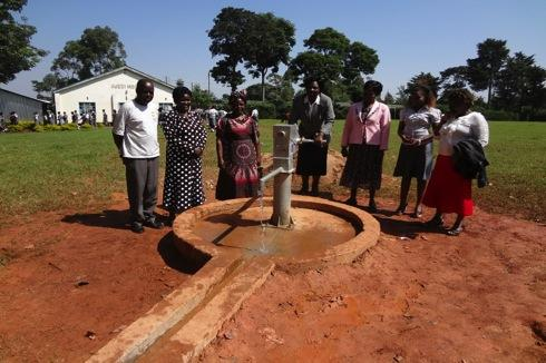 Members of the water committee gather for a picture with the improved water point that
