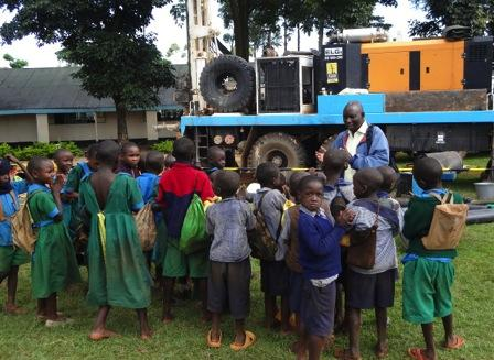 Secondary school children gather at the drill rig to learn about safe hygiene and
