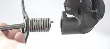 Once the pulley pivot bolt is free, carefully extract the entire pulley cage pivot assembly.