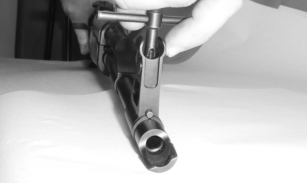 Depress the recoil spring cam until its guide lugs are aligned with the channel on the top of the receiver rear plate.