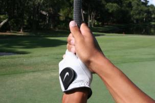 * Place the club diagonally in front of you, across your body. Grip the club in your fingers, making sure the back of your left hand matches the clubface.