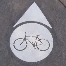 by bicycle. The sign on the right indicates direction and distance.