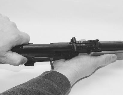 Hold the pistol by the forward portion of the receiver with your hand and with your other hand insert the front edge of the receiver cover into the groove in the back of the gas tube block.