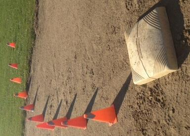 Extend the cones for a distance past the bag before turning to teach the players to run at full speed through the bag. B.