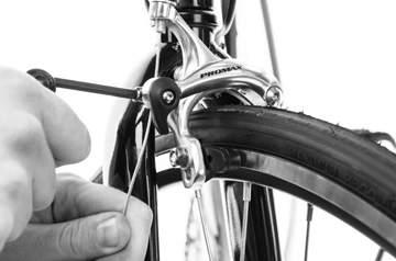 Squeeze the brake arms into the wheel rim so that the brake pads are touching the rim.