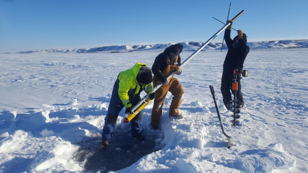 Fig. 7: The single-transponder deployment on the fixed ice was done with simple equipment, and using 3 m long poles.