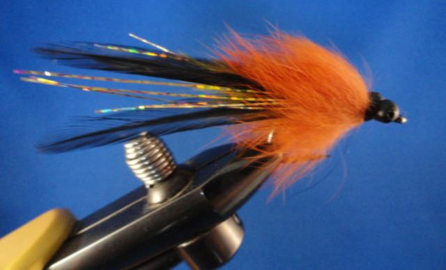 8 FLY OF THE MONTH Redfish Merlot As Tied by Layne Smitty Smith wraps (be sure to stroke fur back after each wrap) up to behind bead chain eyes. Tie down FIRMLY; back wrapping about 3/32 in.