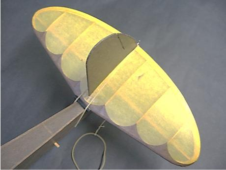 21 A length of thread with a loop is fitted around a wire hook at the aft end of the tail assembly, which is held in place by a rubber band, which looped around the fuselage and either