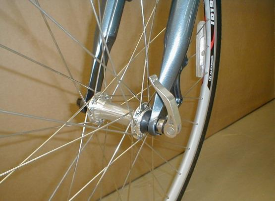 Insert the wheel between the fork blades so that the axle seats firmly at the top of the fork dropouts (1-A), which are at the tips of the fork blades.