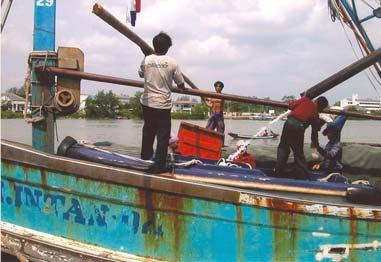Thai crew sorting gear on Kelantan vessel moored at Sungai Patani Red cabin vessel top right are all